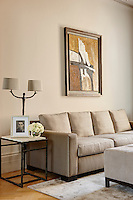 A metal lamp with two shades is placed on a metal side table next to a three-seater sofa upholstered in a neutral fabric.