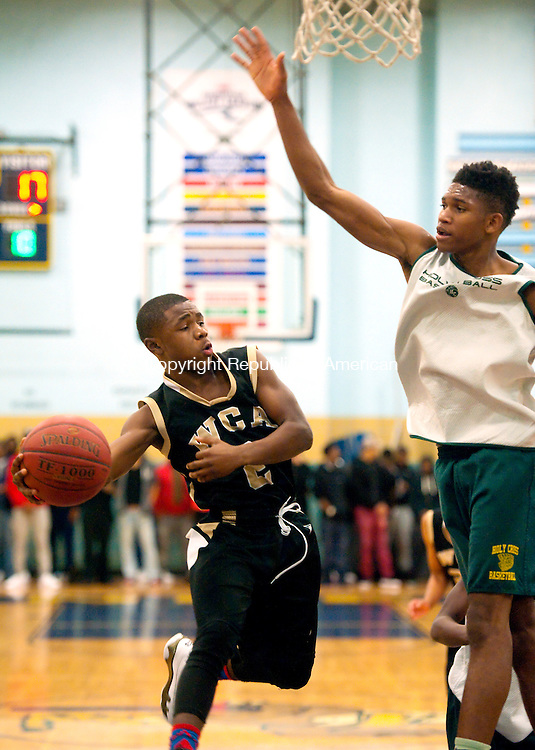 WATERBURY, CT--- -121915JS19--Career Academy's Jayden Battle (2) dishes off the ball while being guarded by Holy Cross' Deandre Wallace (24) during the annual boys basketball jamboree held Saturday at Kennedy High School in Waterbury, <br /> Jim Shannon Republican-American