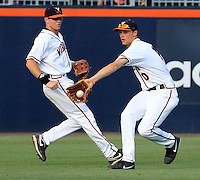 Virginia outfielder Derek Fisher (23) watches as Virginia outfielder Brandon Downes (10) stops a ball up the middle during the game Tuesday night against VCU at Davenport Stadium in Charlottesville, VA. Photo/The Daily Progress/Andrew Shurtleff