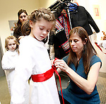 Washington, CT- 29 December 2013-122913CM14  CL ONLY PLEASE----  Karin Fox of Woodbury, helps Ella Viau, 6, of Sandy Hook into costume before the start of a miniature procession of Sankta Lucia, inside the Gunn Memorial Library in Washington on Sunday.   Christopher Massa Republican-American