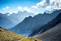 Two women runners descending to Arolla while trail running on the Via Valais, a multi-day trail running tour connecting Verbier with Zermatt, Switzerland.