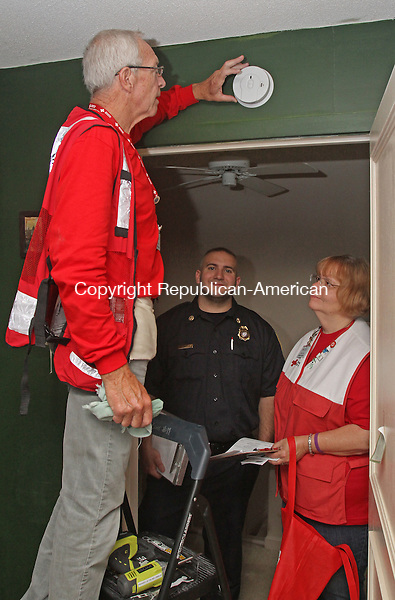 Southbury, CT-071815MK01 Volunteer Arthur Hopkins installs a smoke detector as fellow volunteer Teresa Folgel and Southbury's deputy fire marshal Derrek Guertin look on in Roberta Hade's home at Heritage Village in Southbury Saturday morning.  Deborah Danen, American Red Cross territory-5 project manager, said that four teams set out to install multiple new smoke detectors in ten condos and each detector had a battery that will last ten years before having to be replaced.  Deputy fire marshal Guertin said that the department was on hand to give fire prevention tips and evacuation suggestions as part of the event.  The devices were provided at no charge to the homeowners from a program that American Red Cross receives funds for. Michael Kabelka / Republican-American.