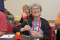 New York, NY, USA - June 24-25, 2017: OrigamiUSA 2017 Convention at St. John's University, Queens, New York, USA. Linda Bogan, New Jersey, learns how to fold an 8 by 8 Grid Rose in a class taught by Heidi Steiger.