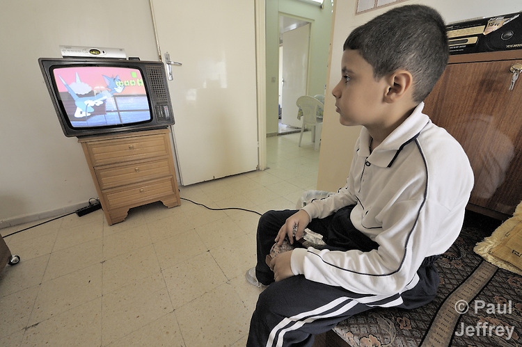 Yousif Abbas, 7, an Iraqi refugee who lives with his family in Damascus, Syria, watches television after getting home from school. More than one million Iraqi refugees are estimated to live in Syria, part of a large diaspora of families who fled the violence of the U.S. occupation.