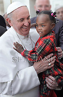 Pope Francis blesses a child  after the Holy mass with the ecclesial movements for Pentecost Sunday on May 19, 2013