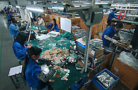 "Factory workers assemble circuit boards at Zhuhai Aimei Electronic Technology Co., Ltd. which is a MP3 and MP4 factory in Zhuhai city , Guangdong Province, China. MP3 players are coveted items among young adults in China. Students and young professionals rank a MP3 at top of their ""must buy"" electronics list in 2006. ."