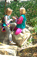 Friends age 10 talking on a rock at Exchange Charities Youth Festival.  Minneapolis  Minnesota USA