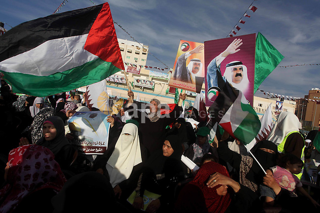 Palestinian Hamas supporters wave Qatari and Palestinian flags as others hold posters of the Emir of Qatar Sheikh Hamad bin Khalifa al-Thani, not pictured, as they wait for him to give a speech at the Palestine stadium in Gaza City, Tuesday, Oct. 23, 2012. The emir of Qatar received a hero's welcome in Gaza on Tuesday, becoming the first head of state to visit the Palestinian territory since the Islamist militant Hamas seized control there in 2007. Photo by Ashraf Amra
