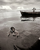 PANAMA, Bocas del Toro, a man freedives and comes to the surface with a crab, his son holds up a fish and a lobster, the Caribbean Sea off the coast of Isla Colon, Central America, (B&W)