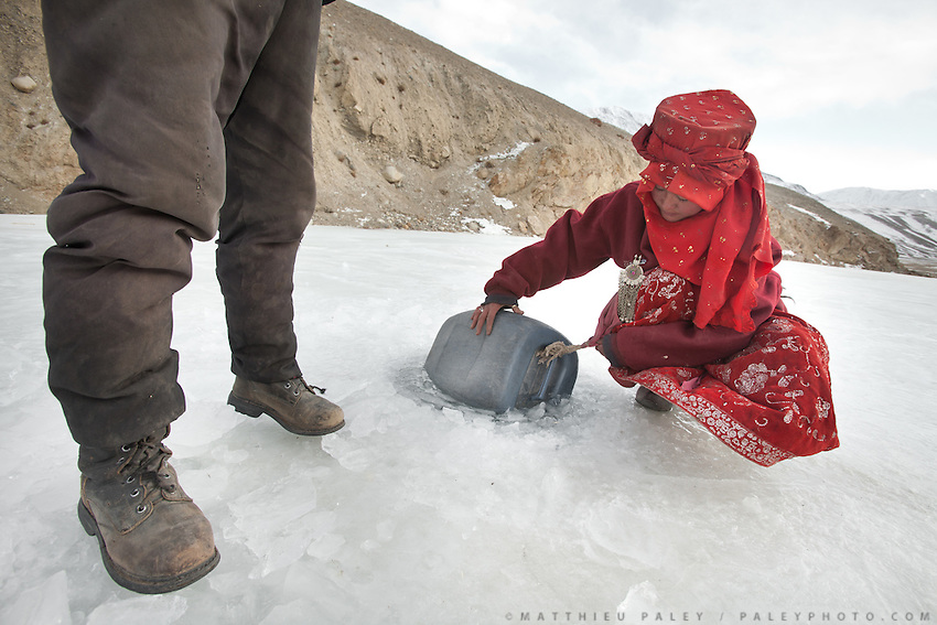 Aslam and Aisha Khan, son and daughter of Mullah Abdul Kassim, fetching water through a hole in the ice near camp. .At the Kyrgyz settlement of Ak Chyktash (Mullah Abdul Kassim's camp, aka Mullah Bachik)...Trekking through the high altitude plateau of the Little Pamir mountains, where the Afghan Kyrgyz community live all year, on the borders of China, Tajikistan and Pakistan.