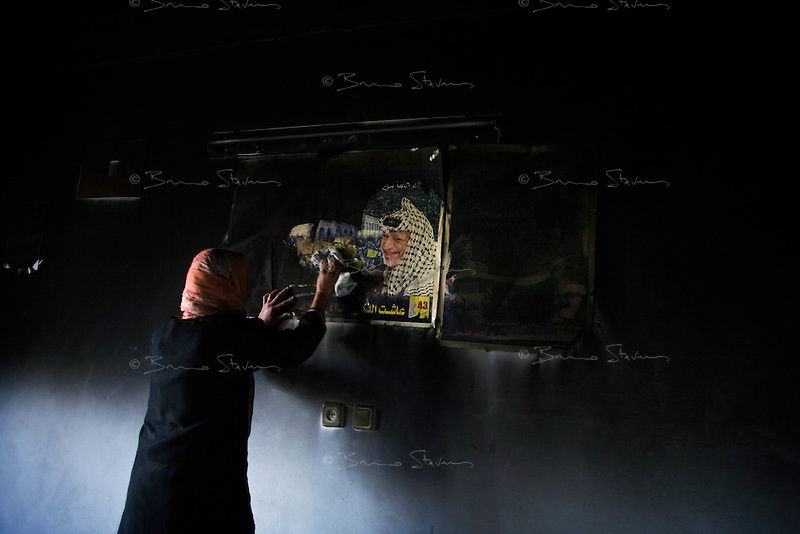 "Al Tuam, Gaza Strip, Jan 21 2009.Alham Al Sultan, 30, wipes away the sooth covering a portrait of Yasser Arafat on the family living room wall. .She says: ""The palestinian people died when Yasser Arafat died""..Inhabitants slowly come back to heavily damaged or totally destroyed homes, as fierce fighting between the Israeli army and Hamas took place in this elevated area just north of Gaza city.."