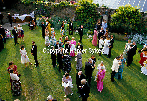 CROWDS AT GLYNDEBOURNE ENJOY THE EVENING SUNSHINE WHILE STANDING ON THE LAWN CHATTING & DRINKING,