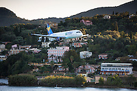 Thomas Cook Condor jet airplane tourist charter flight flying into Kerkyra, Corfu Town, ready for landing, Ionian Islands, Greece