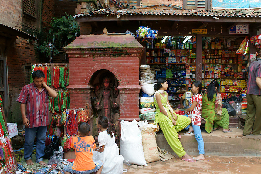street scene in Bhaktapur,Nepal with shop, small shrine, man and children