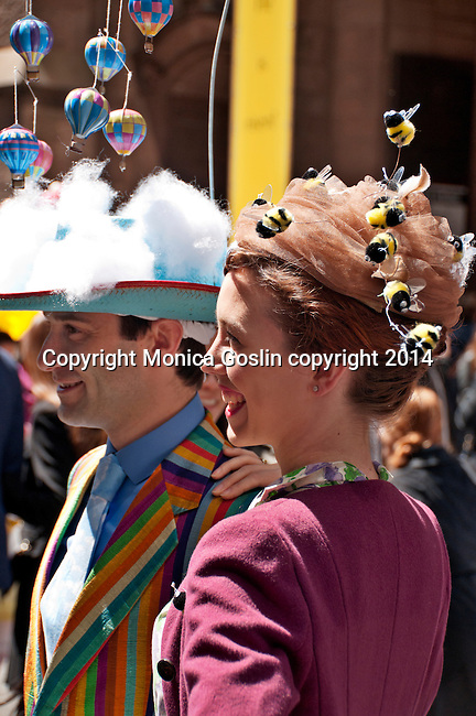 A couple in the Easter Parade in New York City; the man wears a colorful jacket and a hat with clouds and hot air ballons while the woman wearing vintage clothing and a hat with bees all over it for the Easter Parade on Fifth Avenue in New York City