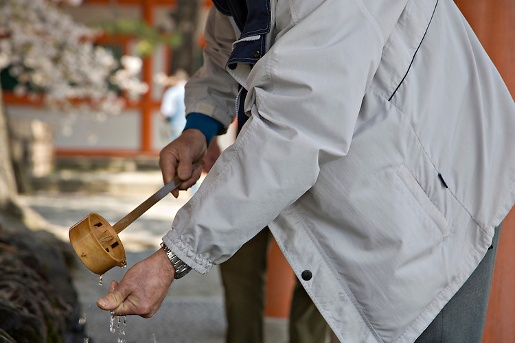 "Man washing hand, called ""temizu,"" at Heian-Jingu Shrine in Kyoto Japan"