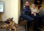 Officer Robert Kornfeld looks on at his dog Friday during the retirment party for the 9 year old dog, sitting next to Kornfield isEast Hartford Town Council Minorite Leader  Donald Pitkin and East Hartford Mayor Melody Currey, Thursday at East Hartford Police Headquaters. A Jim Michaud pic 1-19-06