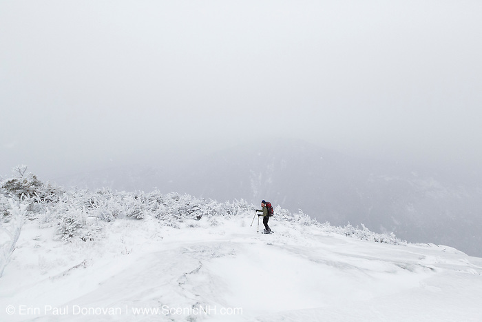 Franconia Notch State Park - Hiker at a scenic view point along Kinsman Ridge Trail in whiteout conditions. This trail leads to the summit of Cannon Mountain in the White Mountains, New Hampshire.