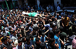 Palestinian mourners carry the body of Mohammed Hamada, 30, who died of his wounds endured during clashes with Israeli troops in a tent city protest where Palestinians demand the right to return to their homeland at the Israel-Gaza border, during his funeral in Jabalia in the northern of Gaza Strip, on June 3, 2018. Photo by Mahmoud Ajour