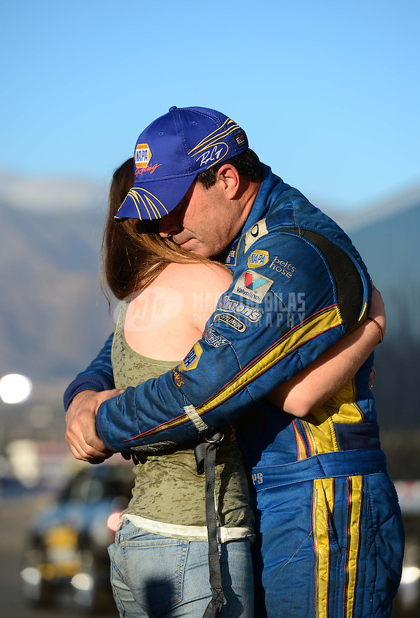 Nov. 11, 2012; Pomona, CA, USA: NHRA funny car driver Ron Capps (right) embraces daughter Taylor Capps after losing the 2012 championship during the Auto Club Finals at at Auto Club Raceway at Pomona. Mandatory Credit: Mark J. Rebilas-