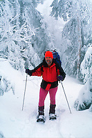 A man showshoes in deep powder as he climbs up scenic Lowe's Path in the White Mountain National Park. New Hampshire.