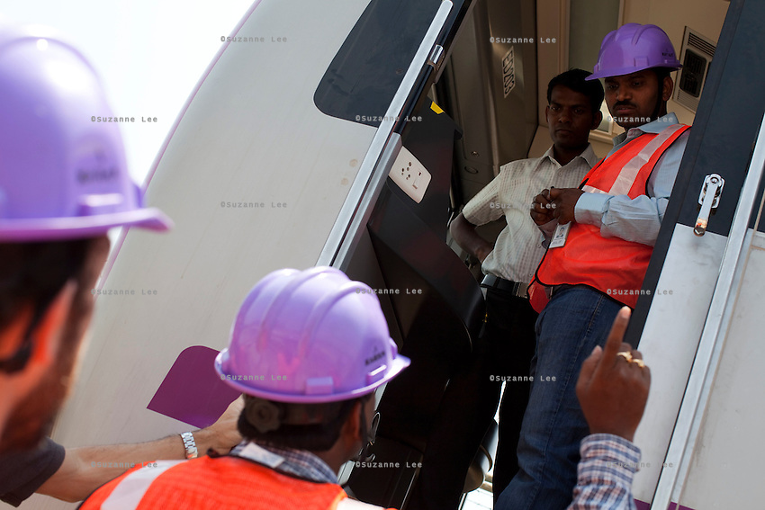 ALSTOM's engineers and employees (in purple hardhats) discuss the project onboard a stationary train in the Baiyappanahalli depot station in Bangalore, Karnataka, India on 10th March 2011. .Photo by Suzanne Lee/Abaca Press