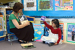 Berkeley CABerkeley CA  Preschool teacher using alphabet cards and pictures to teach student her letters