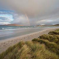 Rainbow shines above sea and coastal sand dunes at Seilebost beach, Isle of Harris, Scotland