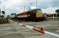 High speed intercity train approaching a railway level crossing. The barriers are down to ensure that no vehicles cross the tracks in front of it.