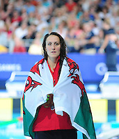 Wales' Georgia Davies walks around with a Welsh flag over her shoulders after taking the silver medal place on the podium in the women's 100m backstroke final when she finished second<br /> <br /> Photographer Chris Vaughan/CameraSport<br /> <br /> 20th Commonwealth Games - Day 3 - Saturday 26th July 2014 - Swimming - Tollcross International Swimming Centre - Glasgow - UK<br /> <br /> © CameraSport - 43 Linden Ave. Countesthorpe. Leicester. England. LE8 5PG - Tel: +44 (0) 116 277 4147 - admin@camerasport.com - www.camerasport.com
