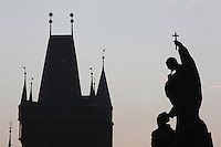 A statue of the Charles Bridge or Karluv most and the gothic Old Town bridge tower, silhouetted against the sky, Prague, Czech Republic. The historic centre of Prague was declared a UNESCO World Heritage Site in 1992. Picture by Manuel Cohen