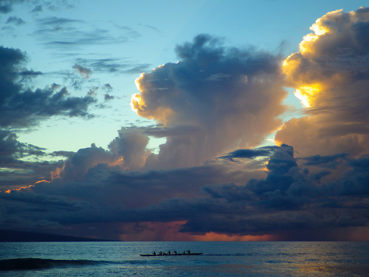 a team of paddlers in an outrigger canoe passing by as storms forming out to sea as visible from kaanapali beach, maui, hawaii