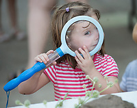 NWA Democrat-Gazette/J.T. WAMPLER Mary Katherine Bridges, 3, gets a close-up look at the world with a large magnifying glass Wednesday July 12, 2017 at the Botanical Garden of the Ozarks in Fayetteville. Little Sprouts is a weekly botanically-themed program for preschoolers at the garden.