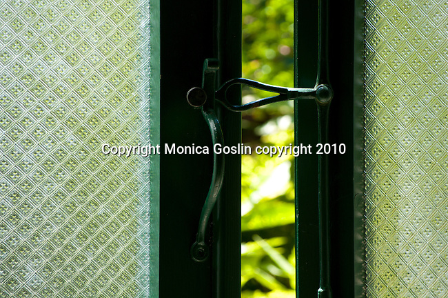 A green lock on a glass door in Ravenna, Italy.