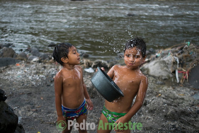 November 07, 2014. &quot;Water it&acute;s the real thing&quot;<br /> A child takes water from a well contaminated in Nejapa (El Salvador). The people of Nejapa in El Salvador, have no drinking water because the Coca -Cola company overexploited the aquifer in the area, the most important source of water in this Central American country. This means that the population has to walk for hours to get water from wells and rivers. The problem is that these rivers and wells are contaminated by discharges that makes Coca- Cola and other factories that are installed in the area. The problem can increase: Coca Cola company has expansion plans, something that communities and NGOs want to stop. To make a liter of Coca Cola are needed 2,4 liters of water. &copy;Calamar2/ Pedro ARMESTRE