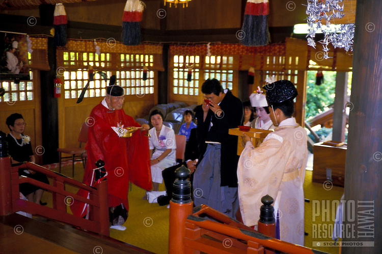 Shinto Buddhist temple and priest performing traditional Japanese wedding ceremony