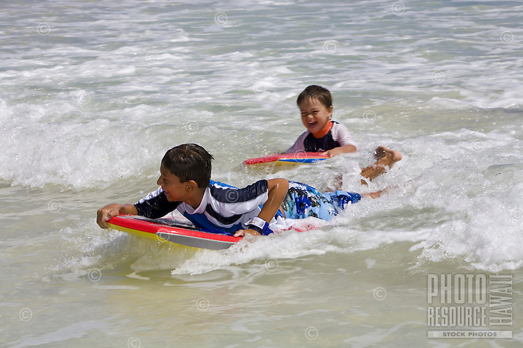 Two boys bodyboard in small waves at Kailua Beach, Oahu, Hawaii.