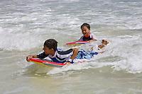 Two boys bodyboard in small waves at Kailua Beach, Oahu, Hawaii.