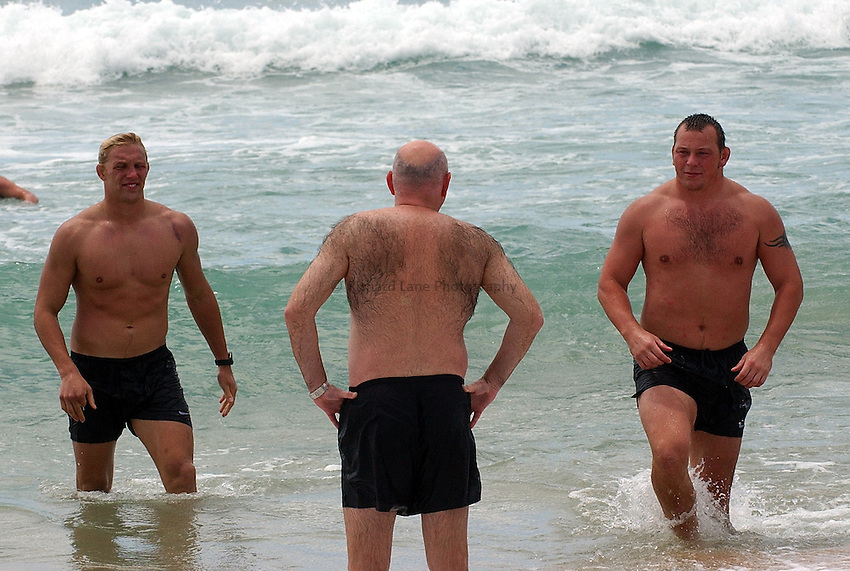 Photo. Steve Holland. England team swim at Manly beach, Sydney. RWC 2003..17/11/2003..L to R Lewis Moody Barney Kenny (physio) and Steve Thompson