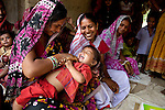 Kanti Devi tickles her daughter Sushma Kumari with Anganwadi health Rita Kumari (right with red and white sari)looking on at a demonstration of oral rehydration salts and zinc tablets in Pakauli village.The village located in Vaishali district outside Patna in Bihar, India has been rolling out the ORS and Zinc program as part of the IKEA Social Initiative to combat child mortality rates caused by diarrhea. It is proving to be very successful with education and support provided by local nursing staff, health activists  and program officers from UNICEF. The treatment is a 14 day course administering diluted oral rehydration salts and a zinc tablet which is more effective than salts alone in combating the effects of severe diarrhea. Picture by Graham Crouch/UNICEF