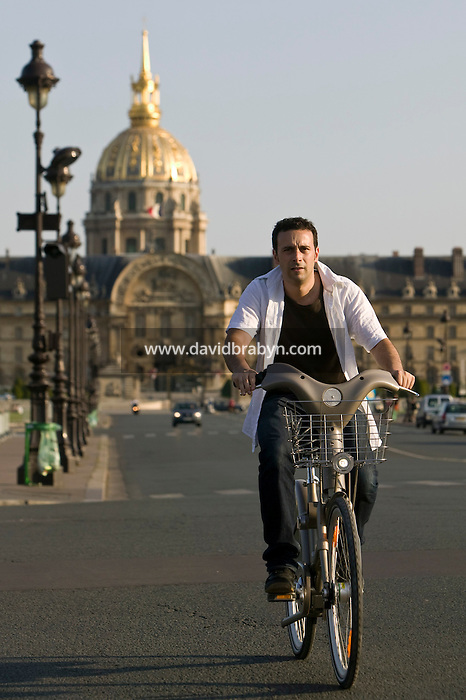 A man rides a Velib' bicycle across the Esplanade des Invalides in Paris, France, 15th July 2007. The city of Paris launched this low-cost self-service bicycle system today with a fleet of 10,000 bicycles.