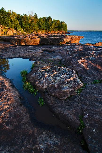 Sunrise over Lake Superior lights up the Madeline Island shoreline at Big Bay State Park, Ashland County, Wisconsin