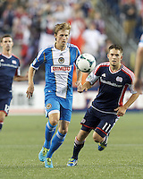 Philadelphia Union midfielder Brian Carroll (7) controls the ball as New England Revolution midfielder Kelyn Rowe (11) closes. In a Major League Soccer (MLS) match, the New England Revolution (dark blue) defeated Philadelphia Union (light blue), 5-1, at Gillette Stadium on August 25, 2013.