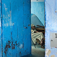 Old man enjoying a nap in his den in the blue city of Chefchaouen