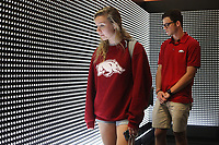 NWA Democrat-Gazette/DAVID GOTTSCHALK Lauren Hacala (left), a sophomore at the University of Arkansas, and Shay Longmate, a junior, walk Wednesday, October 3, 2018, through the Prescribed to Death: A Memorial to the Victims of the Opioid Crisis that features a wall constructed of 22,000 carved pills, each representing the face of someone who fatally overdosed on a prescribed opioid in 2015, inside the Arkansas Union on the campus in Fayetteville. The memorial also offers resources to help visitors both safely dispose of unused pills in their homes and facilitate discussions with prescribers about alternatives. The Associated Student Government is a supporting partner in the exhibit, reserving space on campus and providing volunteers during the week. The exhibit fits in to the ASG's ongoing effort to educate the campus about the danger of opioids. The exhibit is open to the public through Tuesday, October 9.