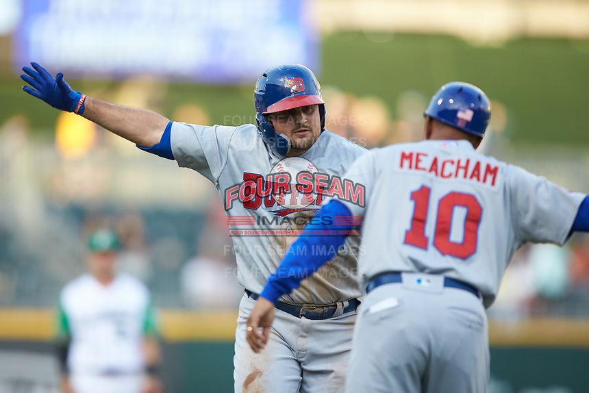 Rowdy Tellez (34) of the Buffalo Bisons celebrates with third base coach Bobby Meacham (10) as he rounds third base after hitting a home run against the Caballeros de Charlotte at BB&T BallPark on July 23, 2019 in Charlotte, North Carolina. The Bisons defeated the Caballeros 8-1. (Brian Westerholt/Four Seam Images)