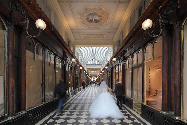 Bride and groom in the Galerie Vero-Dodat, covered shopping arcade built 1826 between the Rue de Jean-Jacques Rousseau and Rue de Croix-des-Petits-Champs, 1st arrondissement, Paris, France. The arcade is Neoclassical in style, with a tiled floor and wooden shop fronts. It was restored in 1997 and is listed as a historic monument. Picture by Manuel Cohen