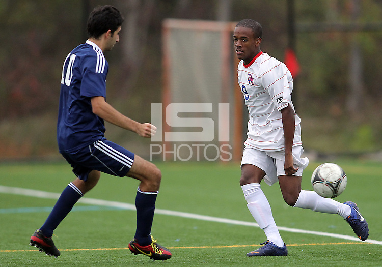 HYATTSVILLE, MD - OCTOBER 26, 2012:  Michael McCoy (9) of DeMatha Catholic High School slips the ball past Arjan Ganji (10) of St. Albans during a match at Heurich Field in Hyattsville, MD. on October 26. DeMatha won 2-0.