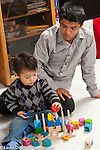 Two year old toddler boy playing with blocks and spindle toy with father