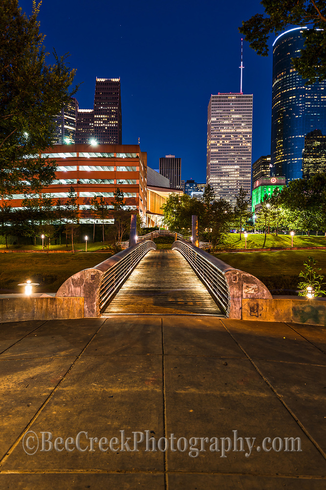 Another capture of this vertical view of the sabine to bagby promenade after dark with the Houston cityscape in view. We like the leading lines with the pedestrian bridge or promenade as they call it.  In this image you can actually see the small bright green building which is the Houston city hall not always viewable in a lot of skyline images in this city.  The downtown is full of many high rise skyscraper and the Well Fargo is the second tallest building in downtown Houston is in view to the right of the walkway.
